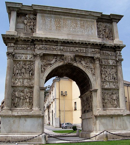 The arch of trajan is a concrete rectagular arch with semioblong hole underneath. It has murals made of different humanoid shapes on the sides and a flat rectagular area with writings in all uppercase on top.